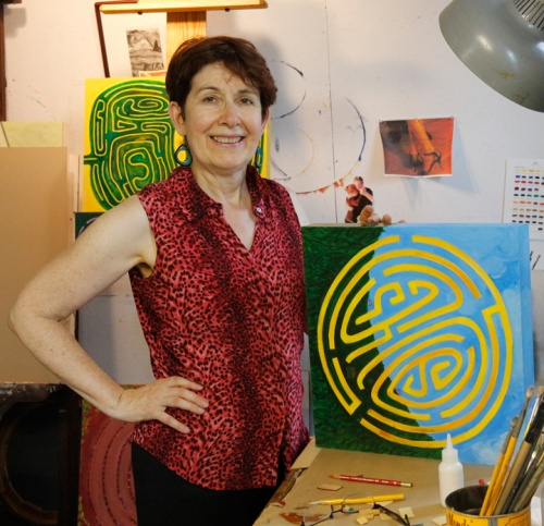Lesley Mitchell in studio with painting, Golden Maze with Houses