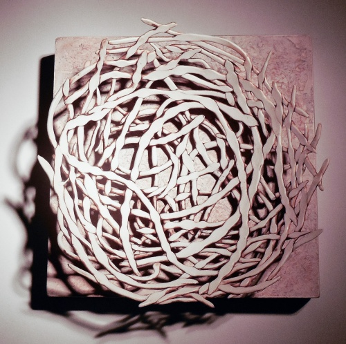 porcelain coiled structure mounted on wood panel